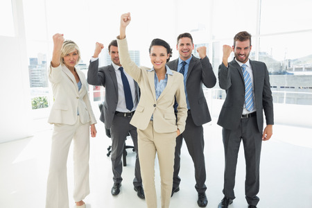 clenching fists: Portrait of a successful business team clenching fists in a bright office Stock Photo