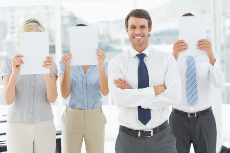Portrait of a smiling businessman with colleagues holding blank paper in front of their faces in a bright office photo