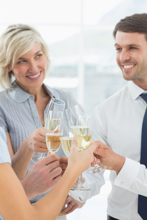 Group of happy business team toasting with champagne in the office photo