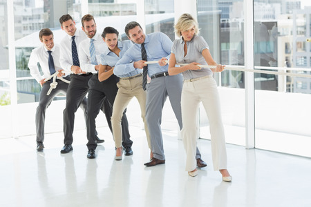 Full length of a group of business people pulling rope in a bright office photo