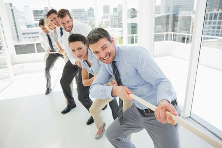 Volledige lengte van een groep van mensen uit het bedrijfsleven touw trekken in een lichte kantoor