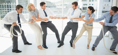 Full length of a group of business people playing tug of war in office photo