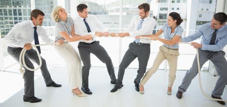 business rival: Longitud total de un grupo de hombres de negocios jugando tira y afloja en la oficina Foto de archivo
