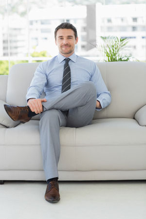 Portrait of a well dressed relaxed young man sitting on sofa in the house