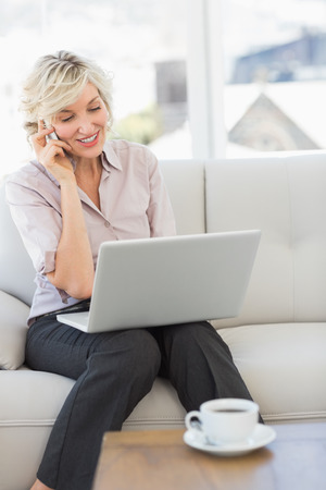 Smiling beautiful businesswoman using mobile phone and laptop at home Stock Photo