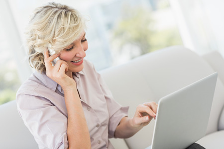 mature adult: Smiling beautiful businesswoman using mobile phone and laptop at home Stock Photo
