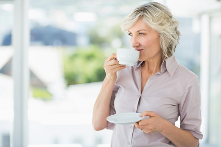 Smiling beautiful businesswoman drinking tea in the bright office photo