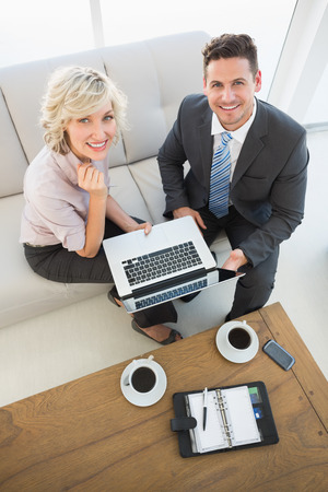 High angle portrait of a businessman and his secretary with laptop and diary sitting on sofa at home photo