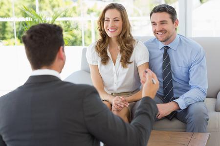 自宅財務アドバイザーとの会議で若いカップルの笑顔