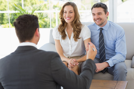 client meeting: Smiling young couple in meeting with a financial adviser at home Stock Photo