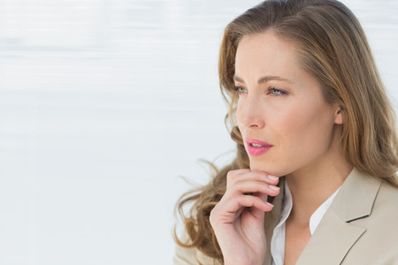 Close-up of a thoughtful young businesswoman looking away against blinds in office