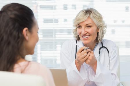 Freundlicher weiblicher Doktor im Gespräch mit Patienten in der Arztpraxis