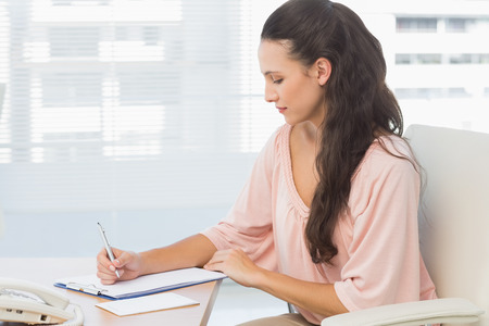 Concentrated young businesswoman writing on clipboard at a bright office Stock Photo - 27075179