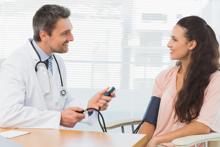 Male doctor checking blood pressure of a young woman at the medical office