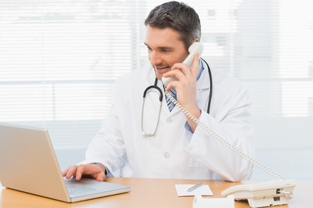 Concentrated male doctor using laptop and phone in the medical office
