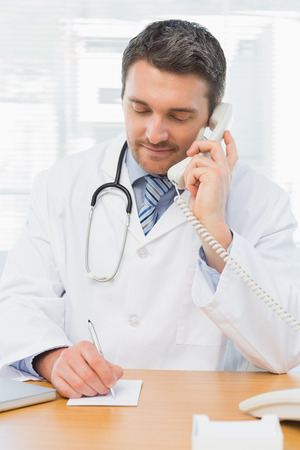 Concentrated male doctor using phone while writing notes at the medical office photo