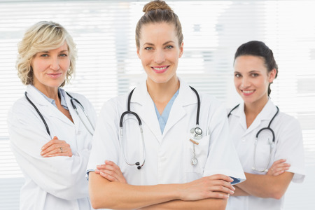 Portrait of three confident female doctors standing with arms crossed at the medical office photo