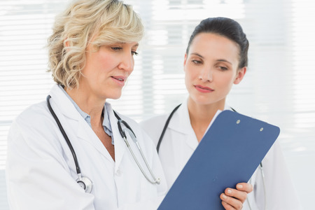 Two female doctors reading medical reports at the hospital photo