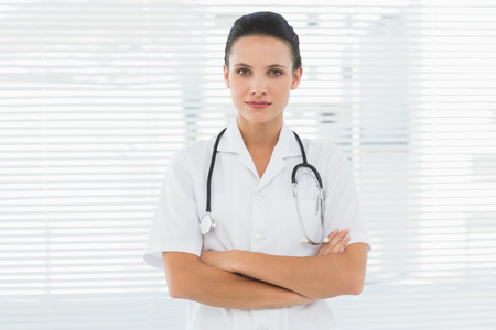 Beautiful young female doctor standing with arms crossed in the hospital photo