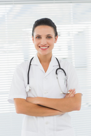 Portrait of a smiling beautiful young female doctor standing with arms crossed in the hospital Stock Photo
