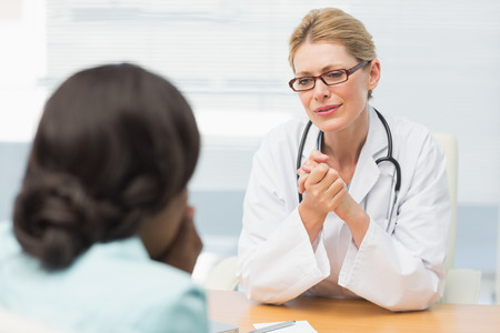 Concerned doctor listening to her patient in an office at the hospital