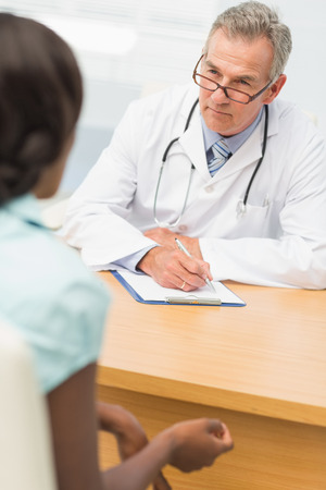 unsmiling: Serious doctor listening to his patient and taking notes in his office at the hospital Stock Photo