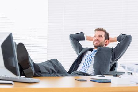 In voller Länge von einer entspannten zuversichtlich, junge Geschäftsmann sitzt mit Beinen auf Schreibtisch im Büro