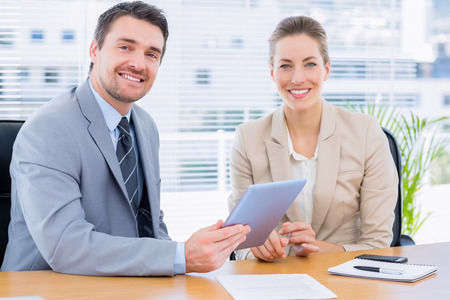 smartly: Smartly dressed young man and woman in a business meeting at office desk
