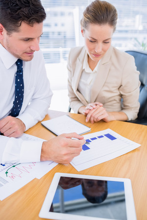 Smartly dressed young man and woman in a business meeting at office desk photo