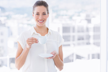 Portrait of a smiling young businesswoman with tea cup standing in a bright office photo