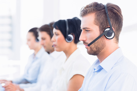 Side view of a group of business colleagues with headsets in a row at office photo