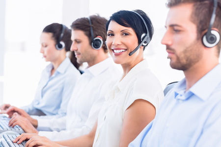 call center office: Side view of a group of business colleagues with headsets in a row at office Stock Photo