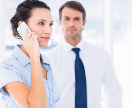 Side view of a smartly dressed young woman on call with male colleague in background at bright office photo