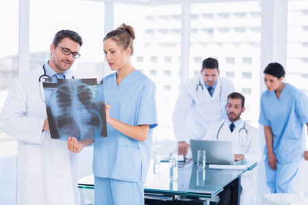 Concentrated doctors examining x-ray with colleagues using laptop behind in a medical office photo