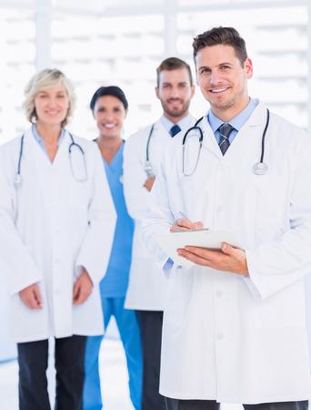 personal medico: Retrato de feliz grupo confía en los médicos de pie en el consultorio médico