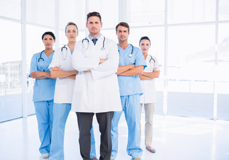 Portrait of serious confident group of doctors standing at the medical office photo