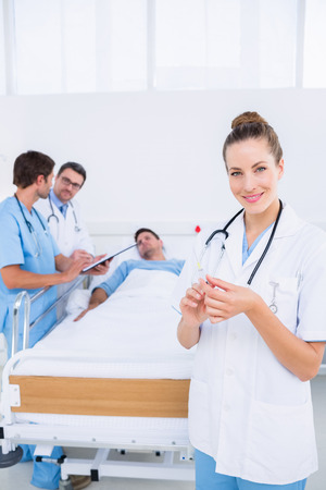 Smiling female doctor holding a syringe with colleagues and patient in background at hospital photo
