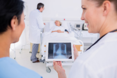 Rear view of doctors examining x-ray with blurred patient in background at the hospital photo