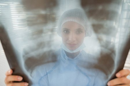 Close-up of a female surgeon examining blurred x-ray in the hospital photo