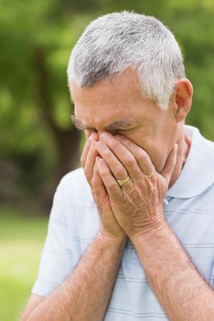 desolaci�n: Hombre mayor preocupante con la cabeza en las manos en el parque Foto de archivo