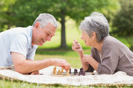 game board: Side view of a happy senior couple playing chess at the park