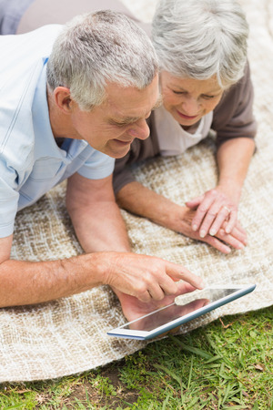 Smiling senior couple using digital tablet while lying at the park photo