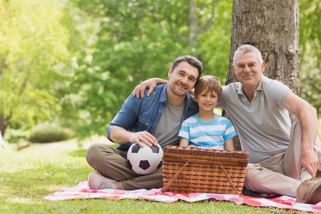Portrait of grandfather, father and son with picnic basket at the park photo