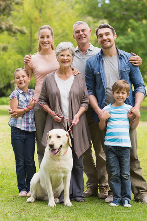 grandparents: Portrait of an extended family with their pet dog standing at the park
