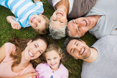 High angle portrait of an extended family lying in circle at the park