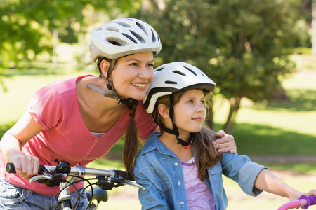Portrait of a smiling woman with her daughter riding bicycles photo