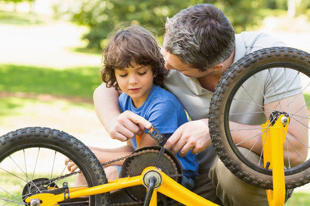 Close-up of father and son fixing bike photo