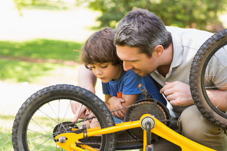 Side view of father and son fixing bike photo