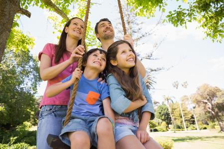 playground ride: Happy couple pushing kids on swing in playground