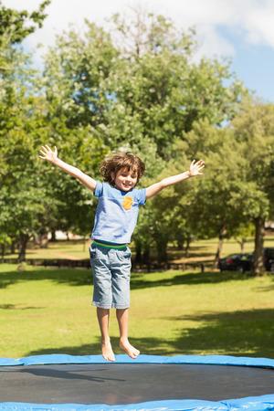 Volledige lengte van een gelukkige jongen springen hoog op trampoline in het park Stockfoto